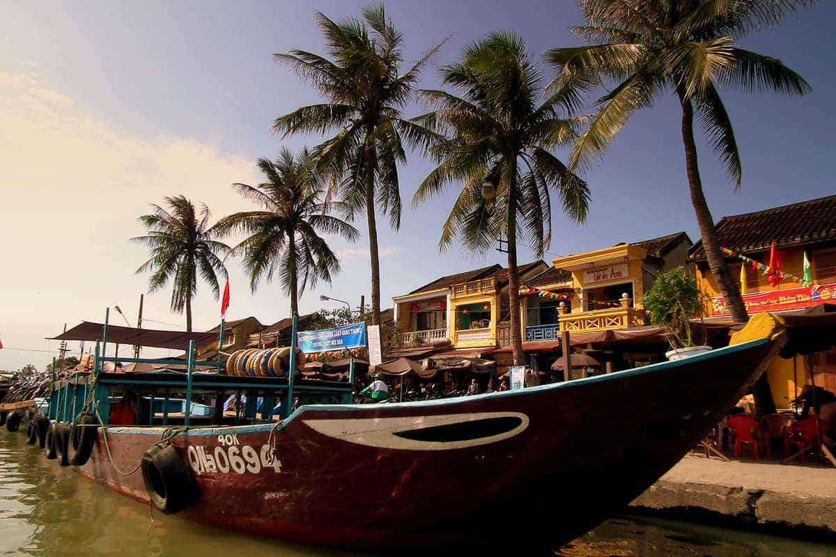 A boat sites at the riverside with palm trees in the background in Hoi An, Vietnam