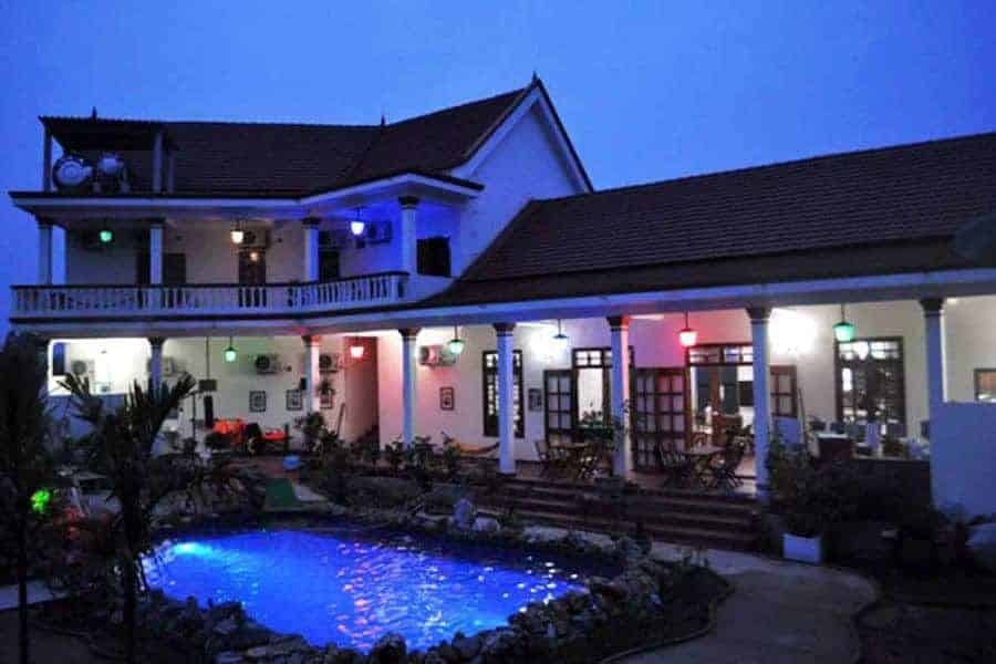 A view at dusk of the pool and the main building at Phong Nha Farmstay