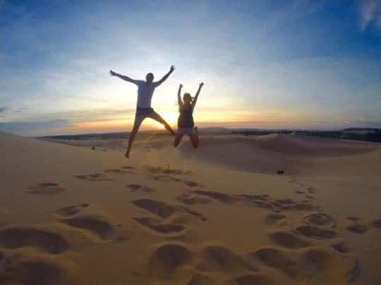 A couple of tourists jump above the sand at sunrise at the white sand dunes, Mui Ne