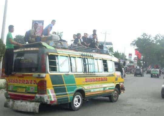 Locals riding on the tops of buses in Sumatra