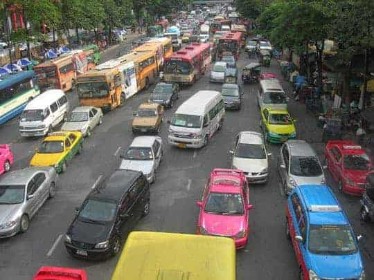 Tuk Tuks weaving through rush hour traffic in Bangkok