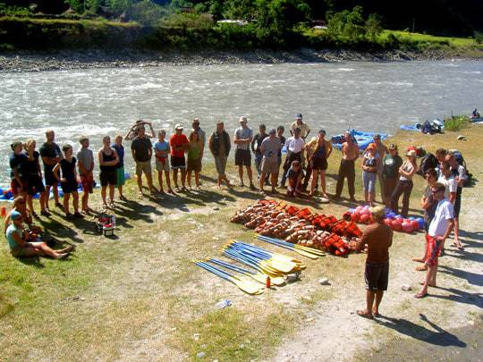 A Big Group of Backpackers Getting Briefed on the Shore Before Setting Off on a Rafting Expedition