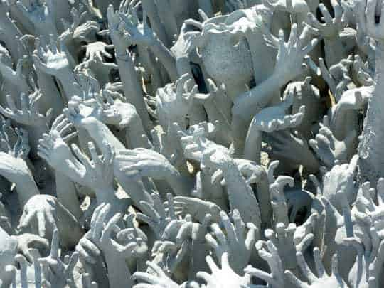 Spooky, ghostly stone hands reaching out of the ground at the White Temple, Chiang Rai, Thailand