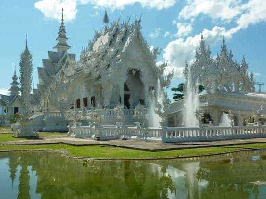 The spiky White Temple and its fountains reflecting in the surrounding ponds of albino fish.