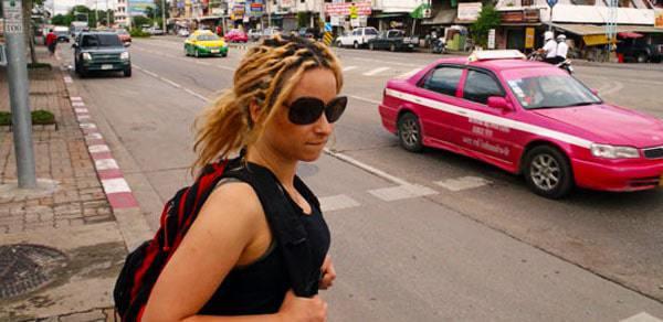A girl walks through Bangkok with a backpack on