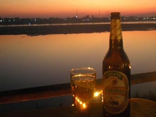 A bottle of Beerlao in the foreground, sunset in the background, Vientiane