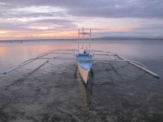 A banca seen in the foreground with a beautiful sunset in Siquijor, The Philippines
