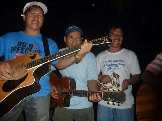 3 musicians serenade tourists on the beach in the Philippines