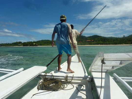 Two men Island hopping on a Banca boat in the Philippines