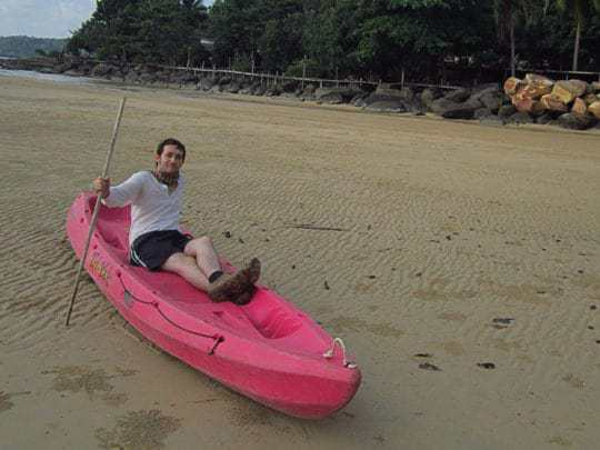 A Man Sits in a Pink Kayak on the Sand (Not the Water) in Koh Kood