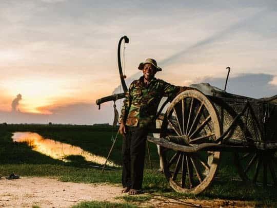 A Cambodian Man Poses Next to an Ox-Cart