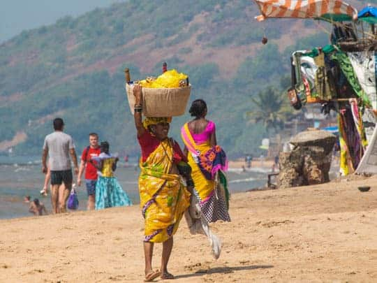 A Beach Hawker Carries a Basket of Wares on Her Head in Goa