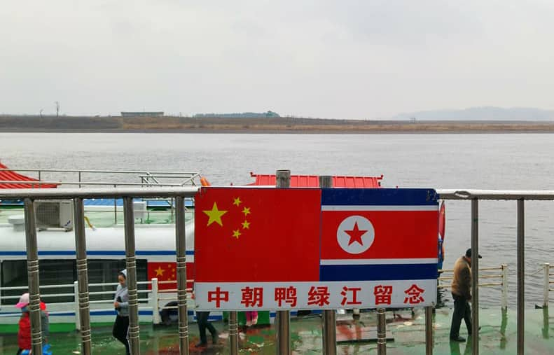 A Chinese Flag Next To A North Korean Flag in Dandong On The River Yalu