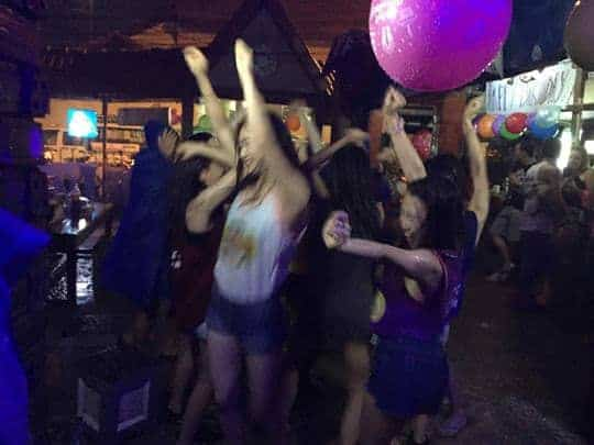 Girls dance in the rain with their arms in the air at sakura bar vang vieng, laos