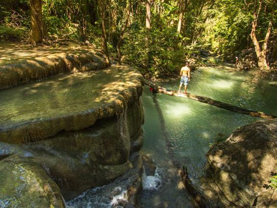 A Man Stands on a Log That Crosses The Water at Erawan Waterfall, Kanchanaburi, Thailand