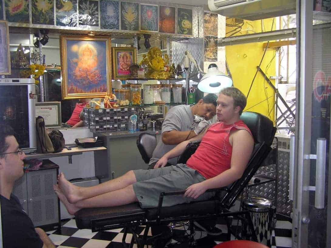 A backpacker sits nervously in Eak Tattoo Shop on Khao San Road, Thailand.