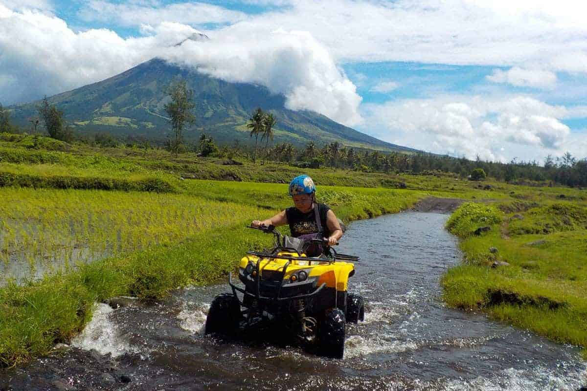 A girl rides a quad bike through a stream in Albay