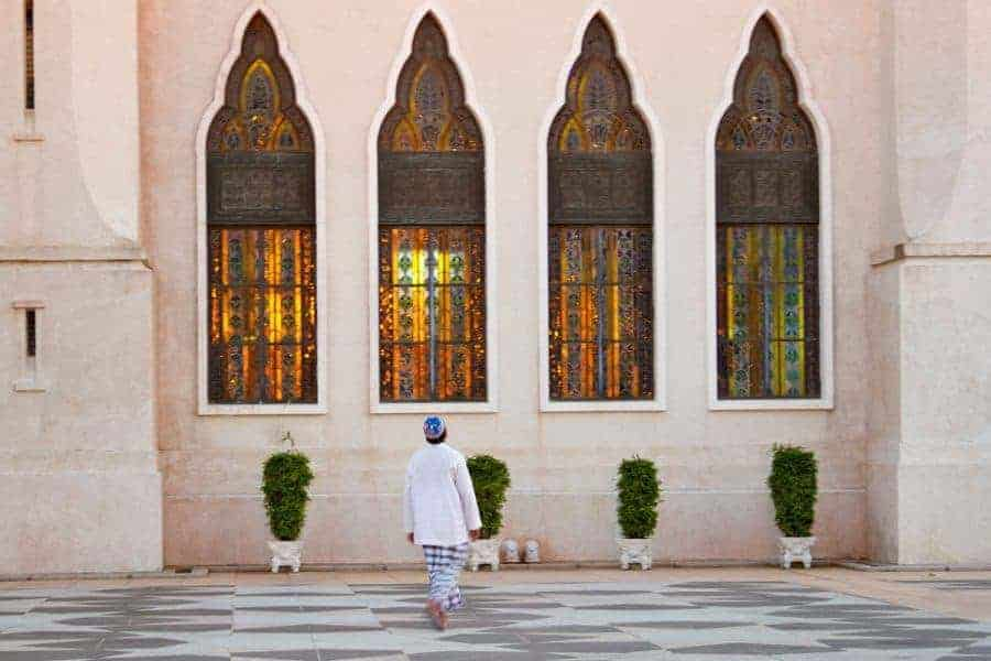 A man stands outside a building in front of four windows in Brunei
