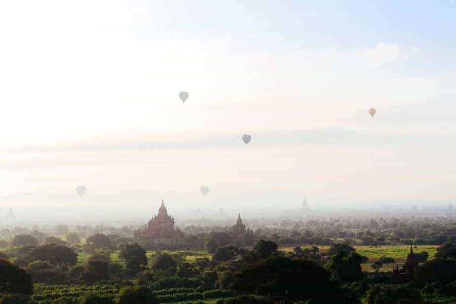 Amazing views over the temples of Bagan with hot air balloons in the distance.