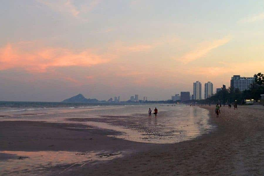 Two people walk on the beach in Hua Hin at sunset