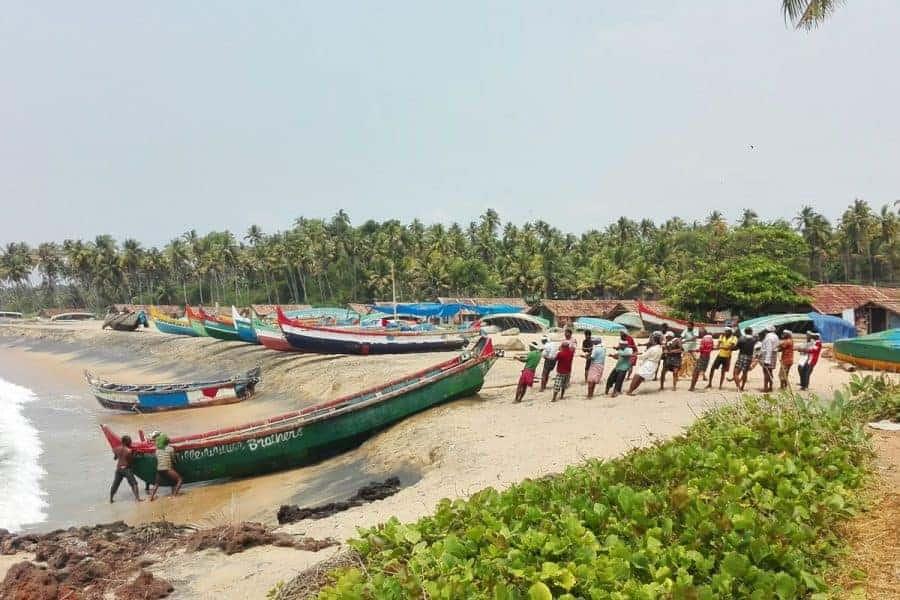 Fishermen pull their boat to shore in Varkala, Kerala