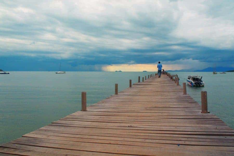 A man walks along a pier on Koh Samui