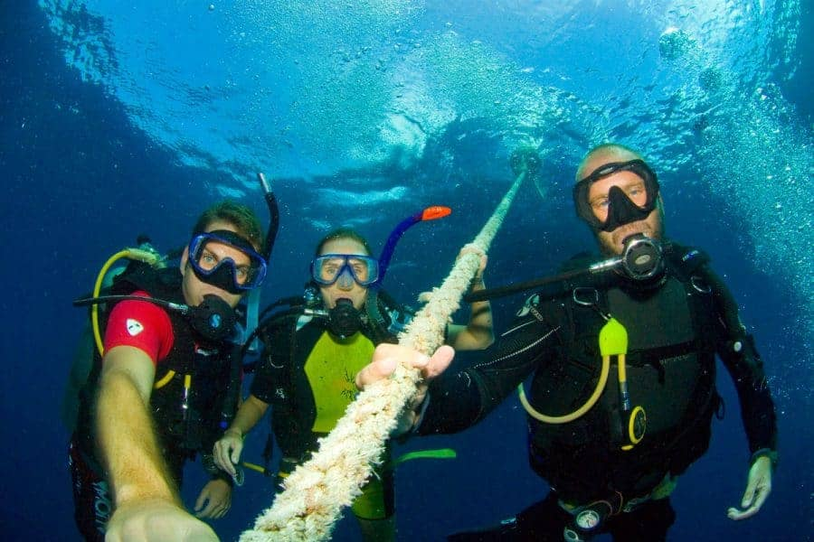 Three SCUBA divers underwater enjoying some of the best diving in Southeast Asia
