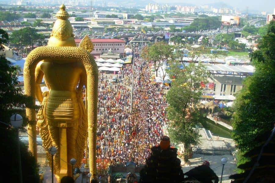 Thousands of people congregate outside the gold statue of Lord Murugan at the Batu Caves, Kuala Lumpur.