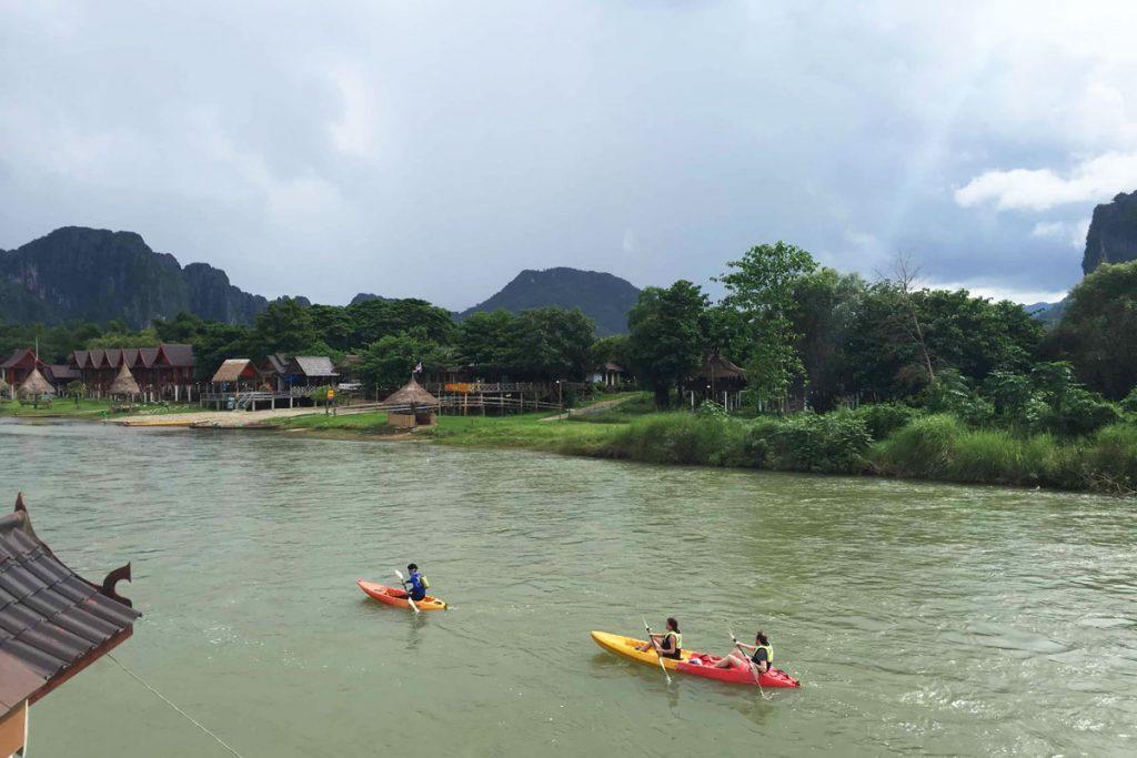 Three people in kayaks row down the river in Vang Vieng, Laos