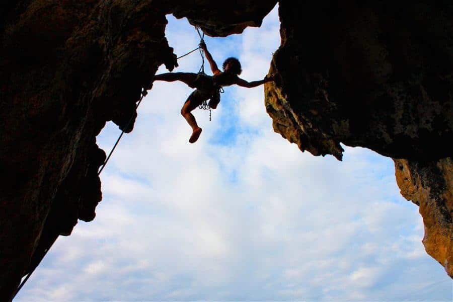 A shot from below of a climber straddling two rocks