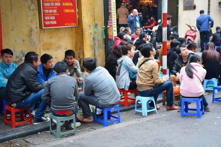 Vietnamese people sat on stools drinking beer at Bia Hoi Junction
