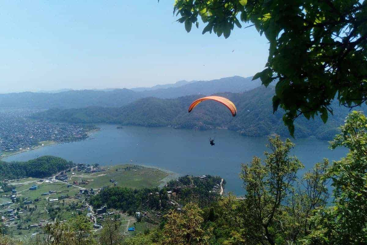 A paraglider seen from Sarangkot, looking towards Phewa Lake, Pokhara, Nepal