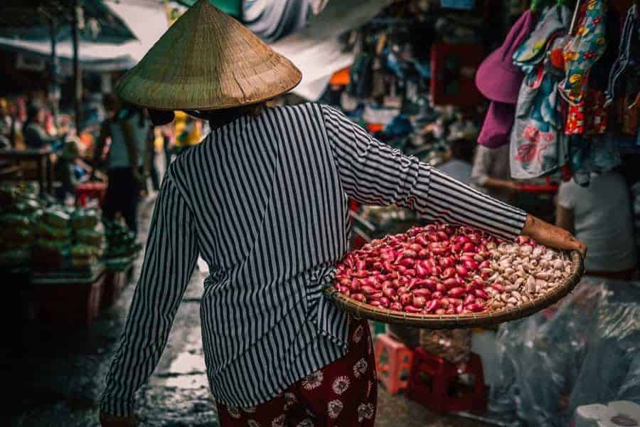 A woman, seen from behind carries a tray of onions in a market in VietnamCheapest Place in Southeast Asia