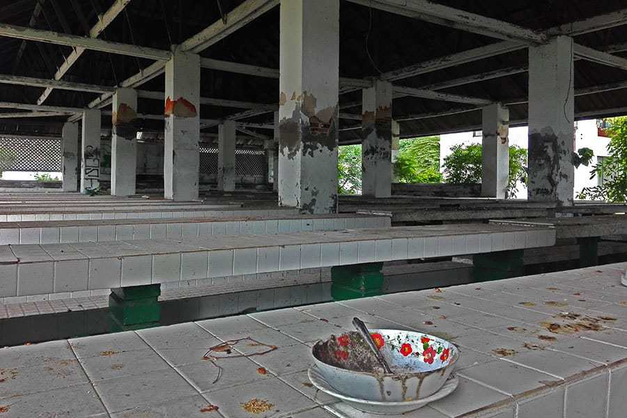 A-dirty-bowl-sits-in-the-foreground-in-a-shot-of-the-dining-room-at-the-abandoned-women's-prison-in-Chiang-Mai,-Thailand
