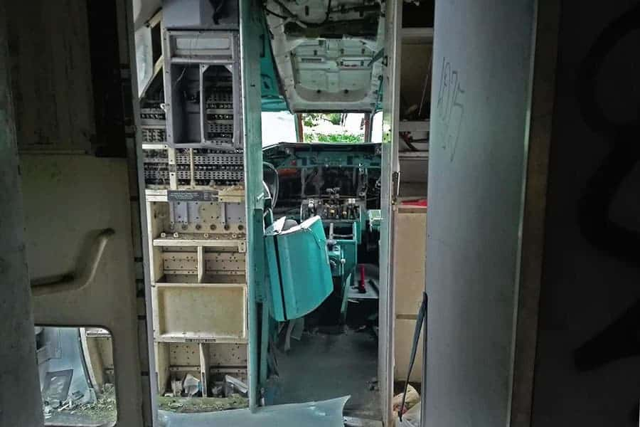 A-view-into-the-cockpit-and-past-the-main-door-aeroplane-graveyard,-Bangkok,-Thailand