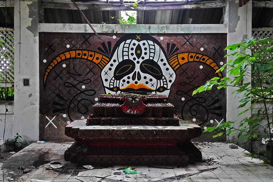 Graffiti-behind-the-altar-found-in-the-dining-room-of-the-abandoned-women's-prison-in-Chiang-Mai,-Thailand