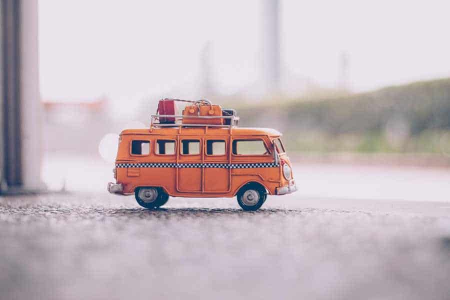 A toy VW van with backpacks on the roof. A comical image to represent a backpack on wheels