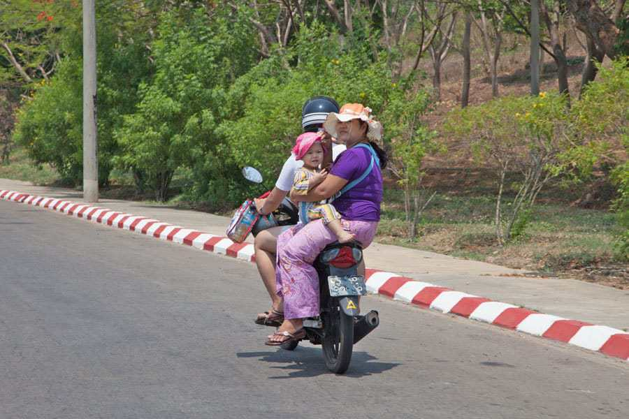 Empty roads and few people. A family travel by motorbike in Naypidaw, Myanmar.