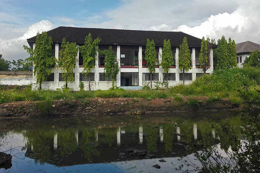 The-biggest-cell-block-seen-across-the-water-at-the-abandoned-women's-prison,-Chiang-Mai