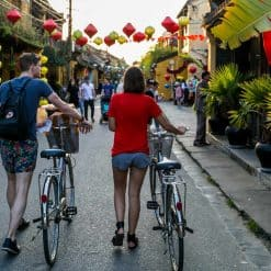 Two travellers push bicycles through the streets of Hoi An.