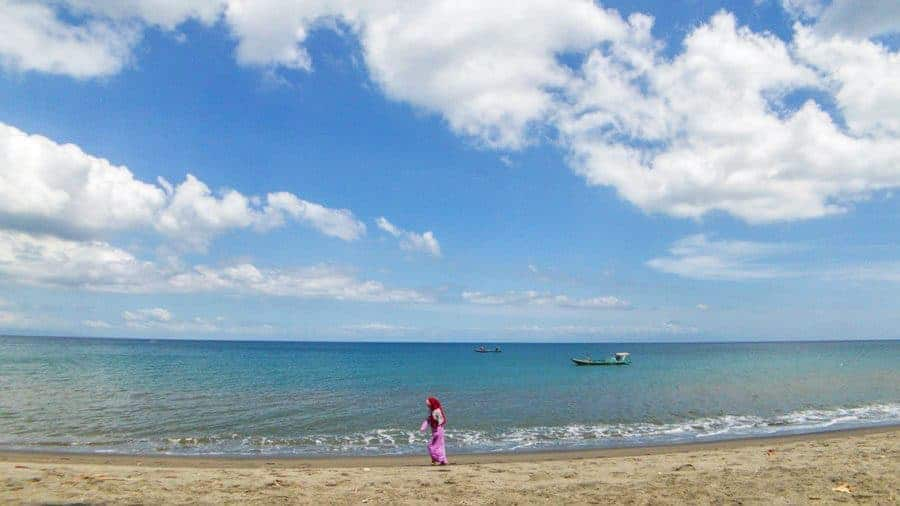 A Local Woman Walks Alone Along Senggigi beach