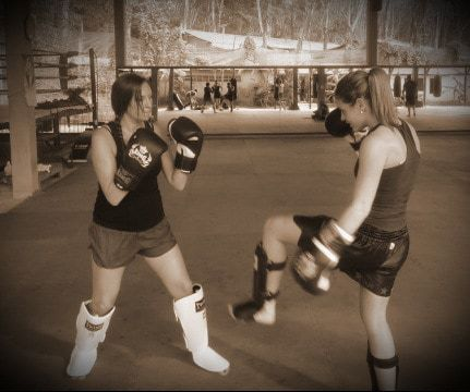 Two students learn various MMA techniques in a Muay Thai class