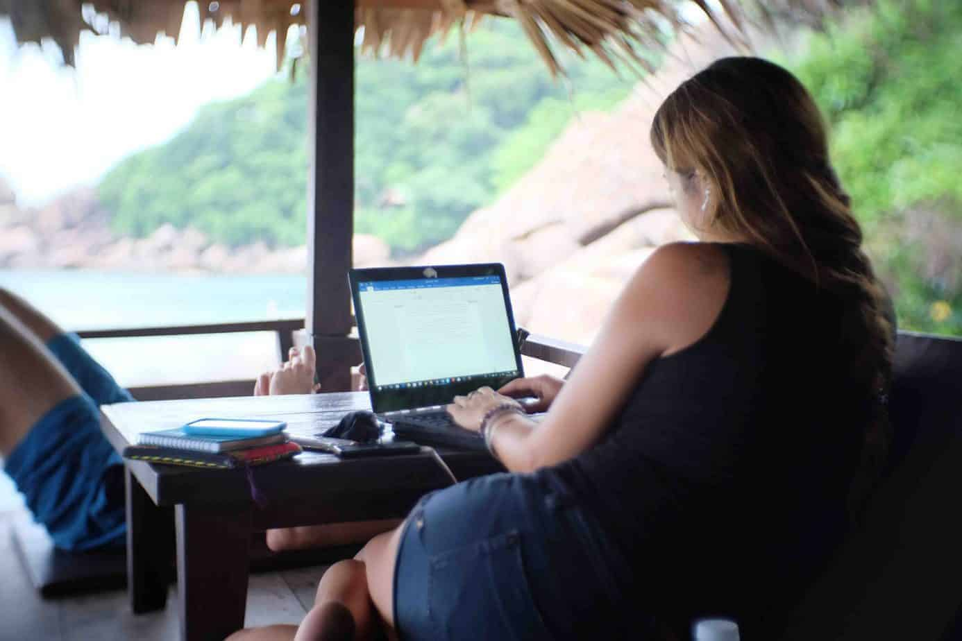 A digital nomad works on her laptop in Southeast Asia.