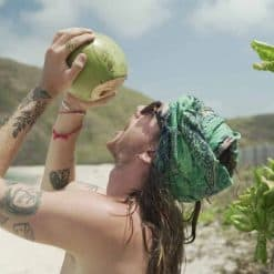 Fresh from the tree! Traveller drinks a coconut on the beach