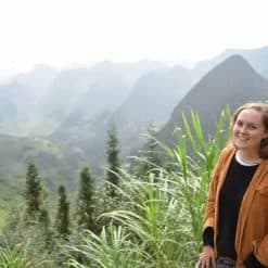 The author poses in front of a valley in Ha Giang.