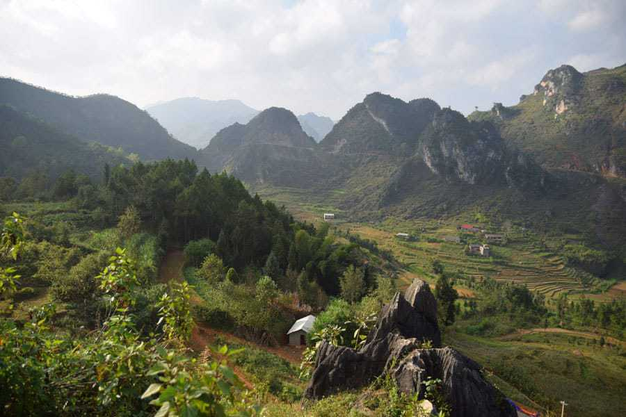 Black rocks jut out in a valley, Ha Giang Loop
