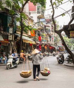 A vendor carrying baskets of food Hanoi, Vietnam