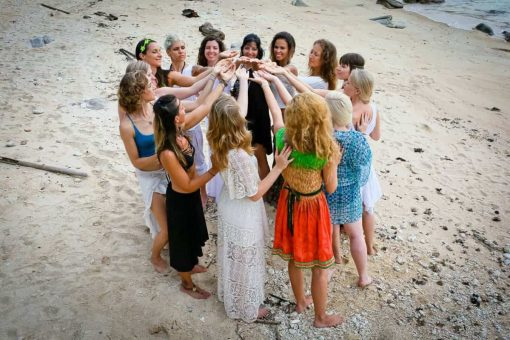 Women in a circle on the beach.