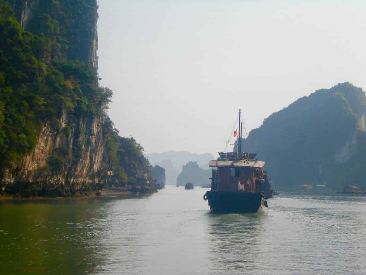 A boat trundling off on a tour of Halong Bay...
