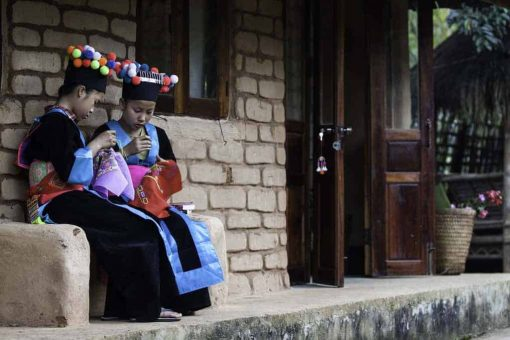 Tribal girls sit by bungalow, Northern Laos.